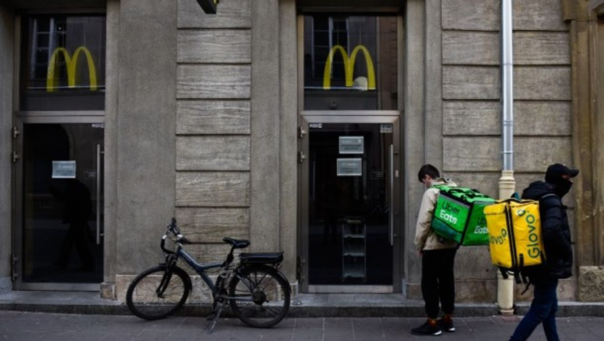 UberEats and Glovo workers wait for McDonald's meals to deliver to their costumers.