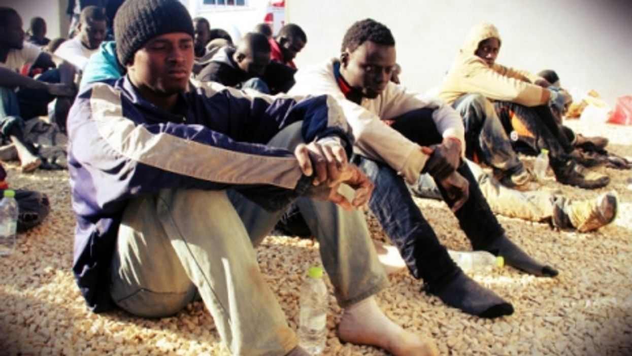 Undocumented immigrants sit in a yard guarded by Libyan police in Tripoli
