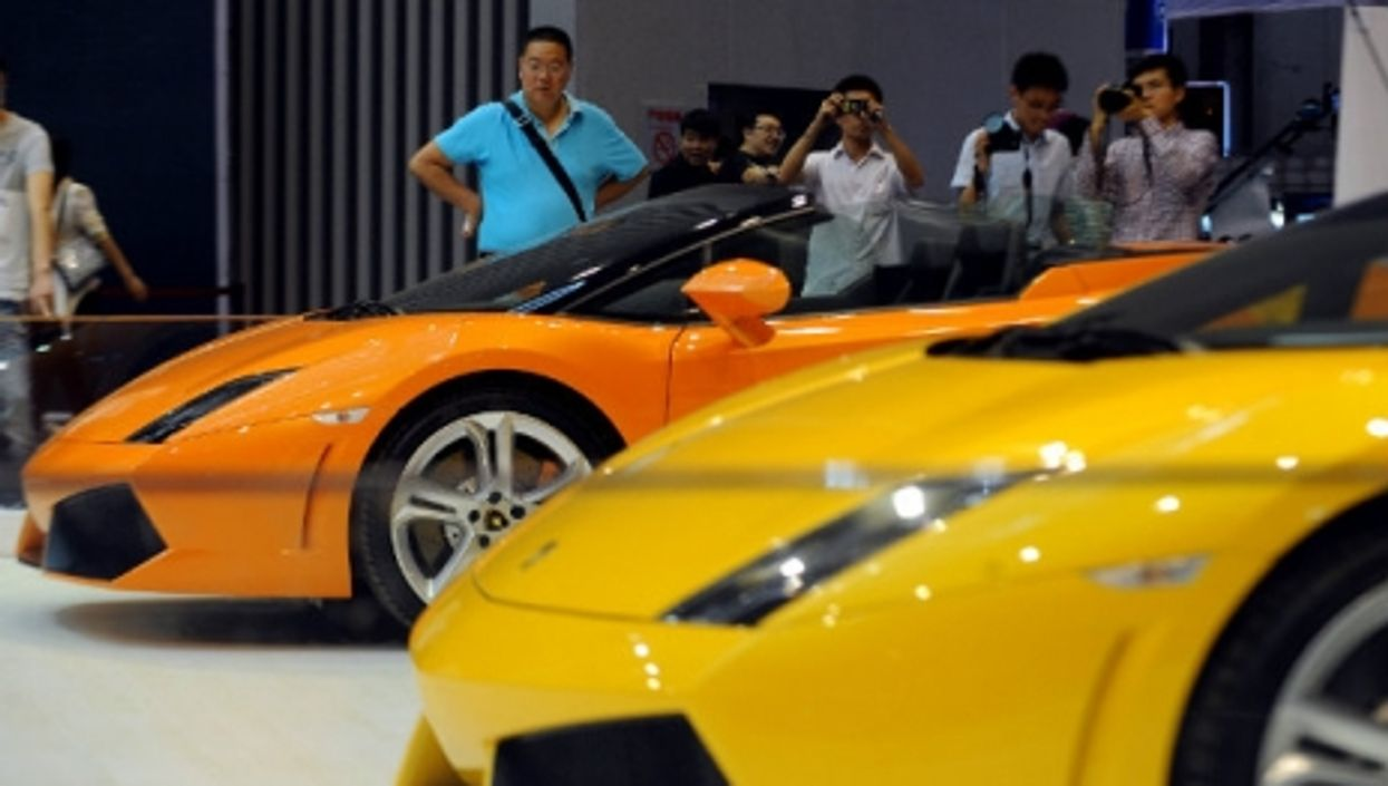Visitors view Lamborghini sports cars at the 2013 International Automobile Exhibition in Taiyuan.