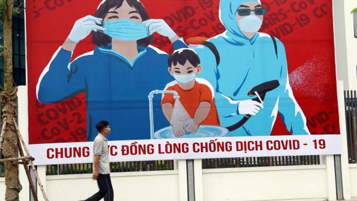 Waking past a billboard in Hanoi, Vietnam, on April 1