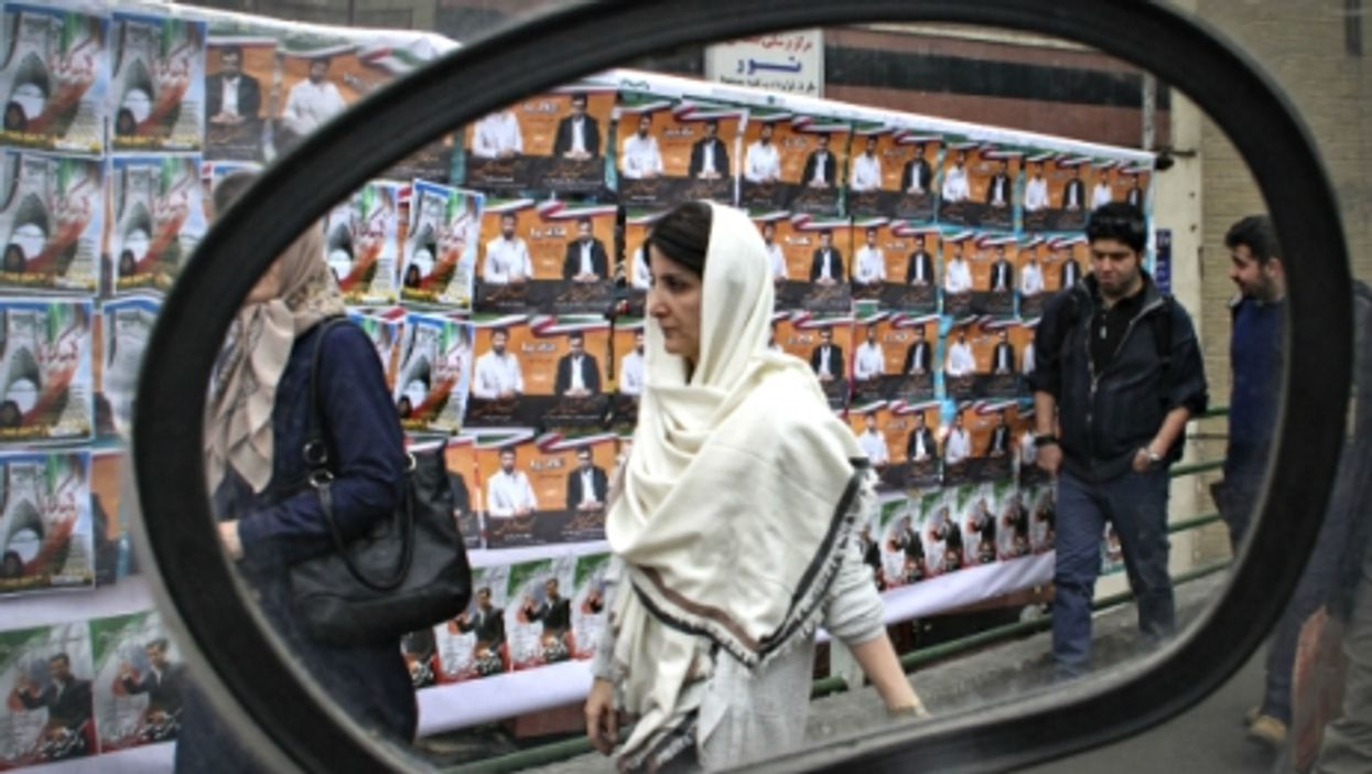 Walking past electoral posters in Tehran on Feb. 22