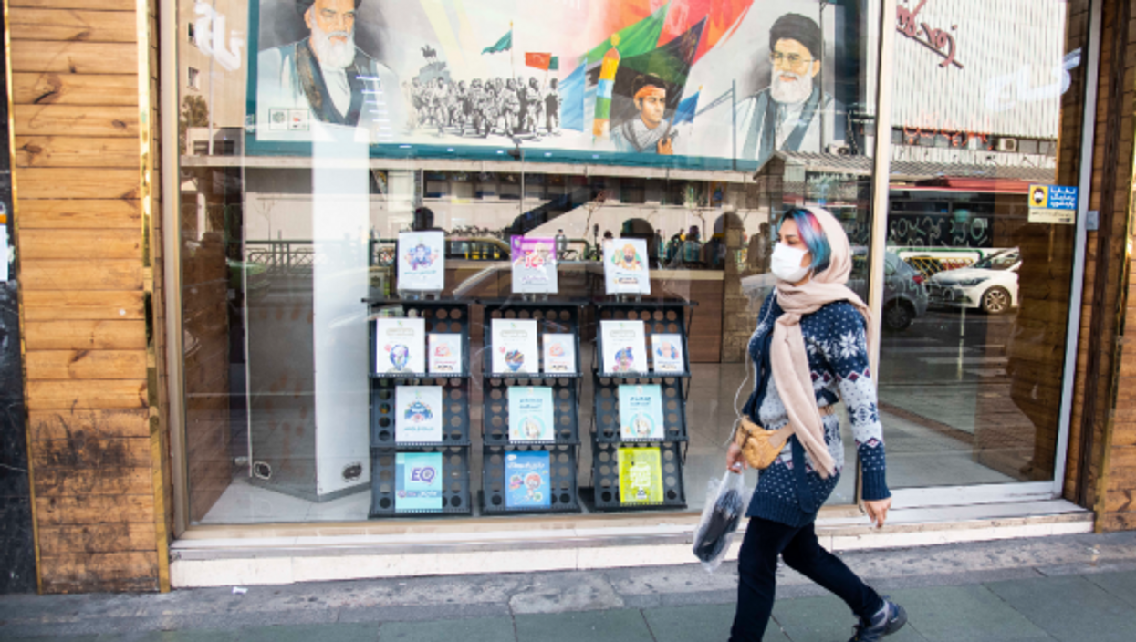 Walking past portraits of Khamenei and late Ayatollah Khomeini in Tehran