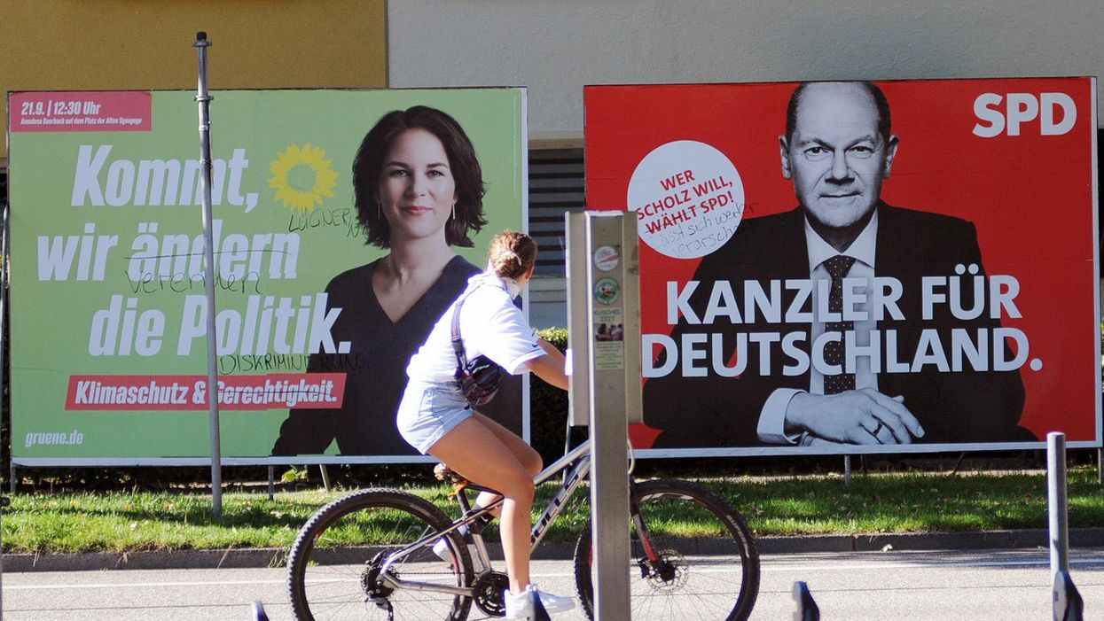 Woman cycling past election posters of Green and SPD candidates