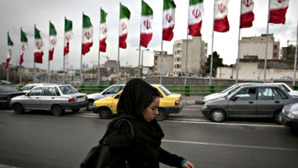 Woman walking in a busy Tehran street