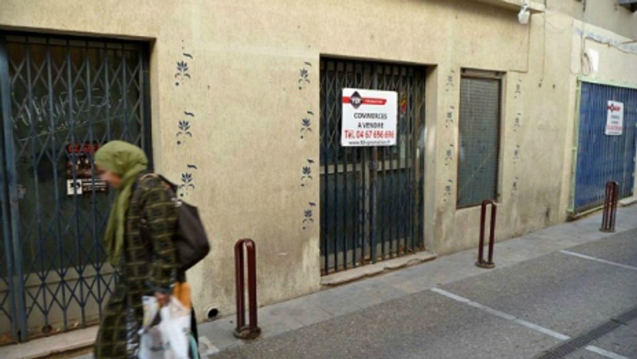 Woman walking in an empty street in Lunel, southern France