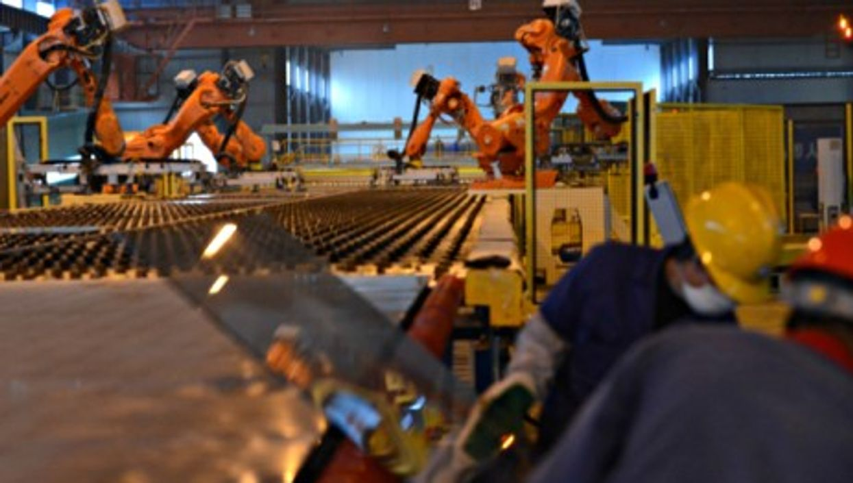 Workers and robots on a production line in Zhangshu, eastern China