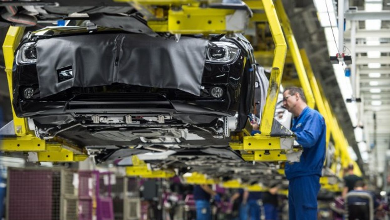 Workers assemble cars at a BMW factory in Germany. Some believe that technological progress has stagnated.
