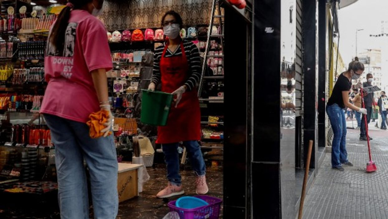 Workers clean a shop before opening in Sao Paulo