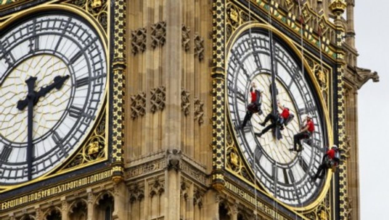Workers clean the clock face of Elizabeth Tower, which houses Big Ben, in London yesterday.