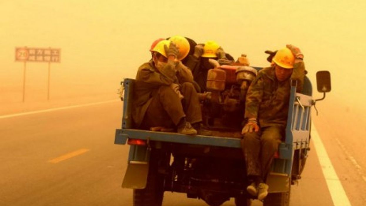 Workers facing a sandstorm Wednesday in southwestern China's Gansu province