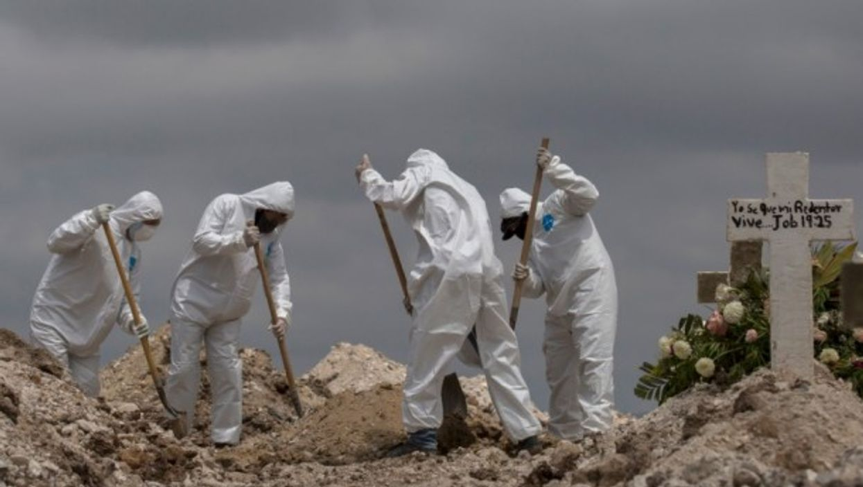 Workers in protective suits are shoveling earth at a funeral in Mexico, Tijuana.