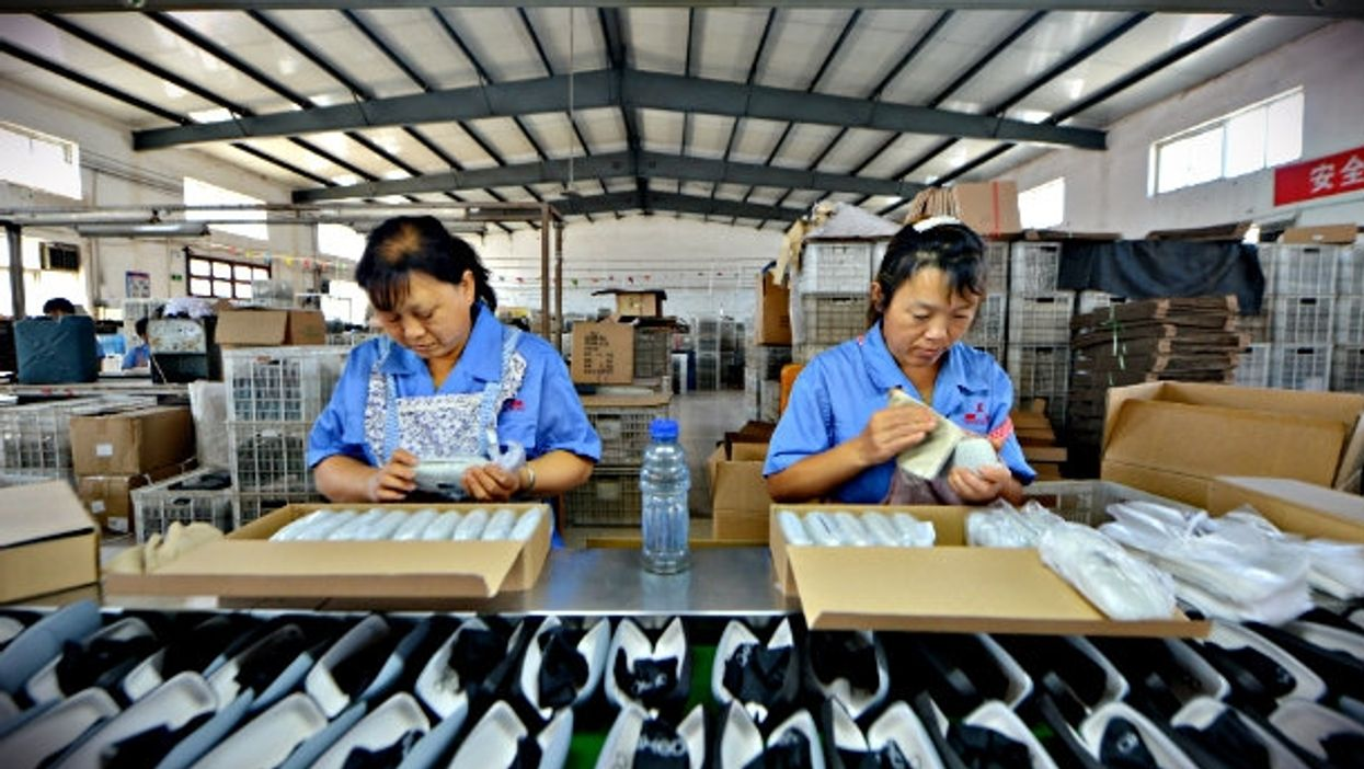 Workers producing glasses cases in a factory in Hebei Province