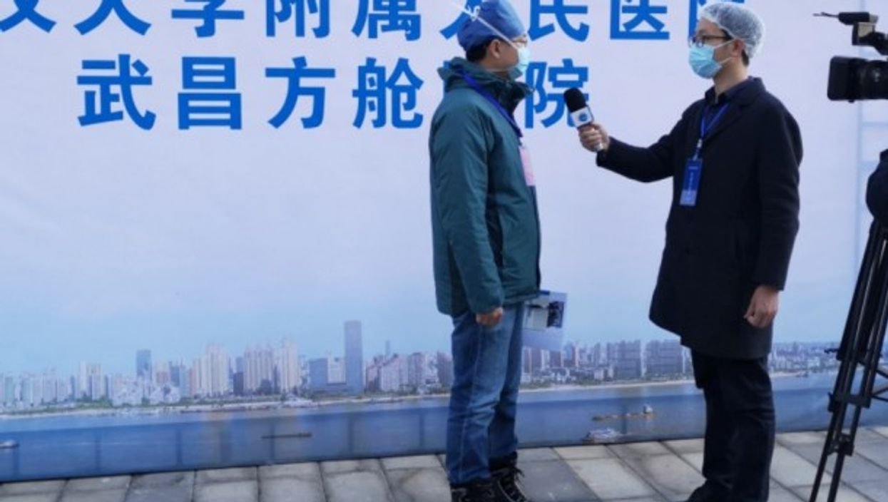 Xinhua News Agency journalist Liang Jianqiang makes an interview at a temporary hospital in Wuhan.