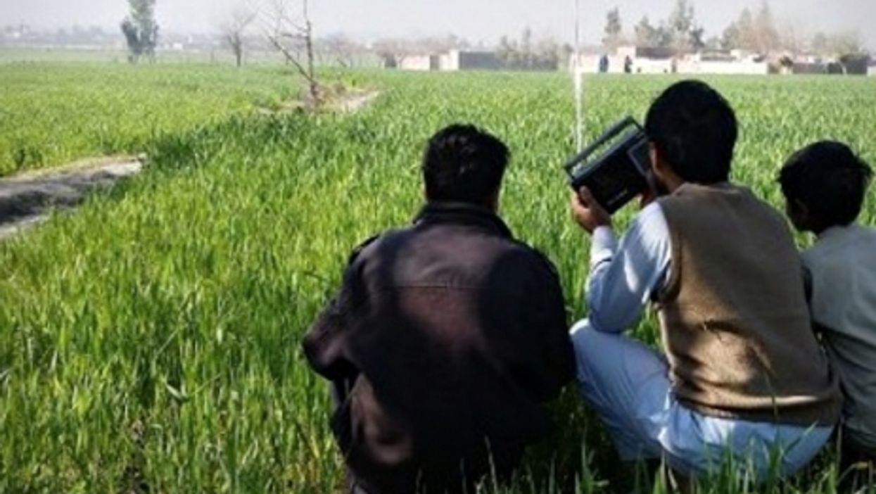 Young Afghans listening to the radio in a field
