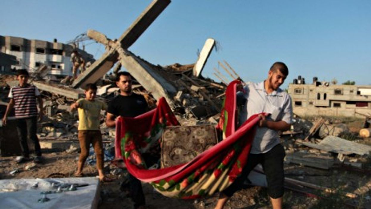 Young Palestinians carry their belongings as they walk past the rubble of their family's house destroyed by an Israeli air strike in Gaza.
